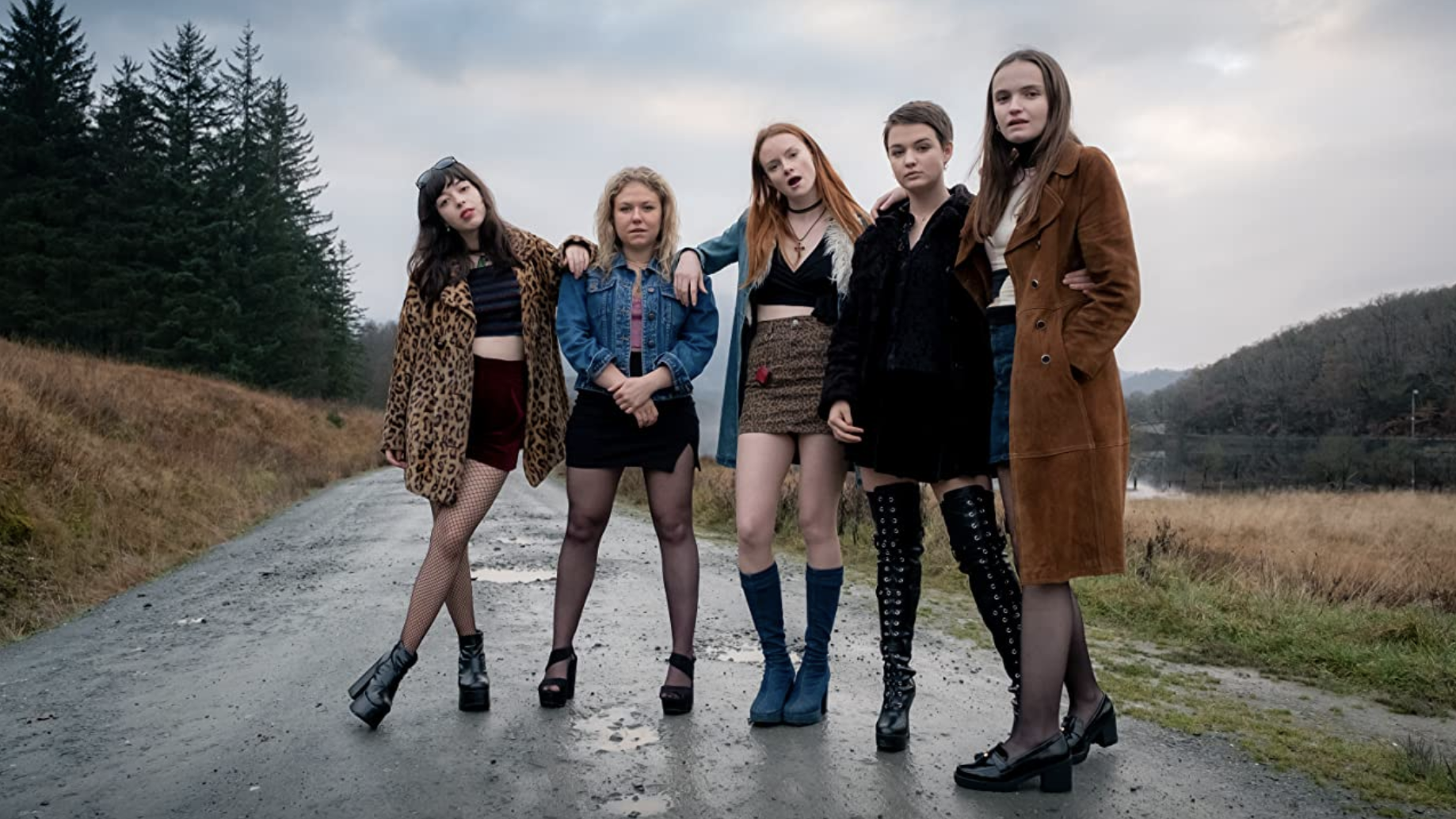 The five main characters of Our Ladies standing on a rural road.